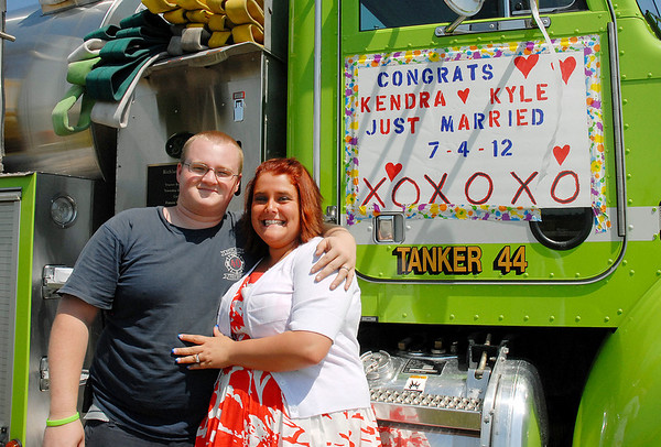 Newlyweds Kyle and Kendra James stand by a Richland Township firetruck before riding in the Chesterfield 4th of July Parade. Kyle and Kendra were married earlier in the morning making Kyle the third generation from his family to wed on Independence Day.