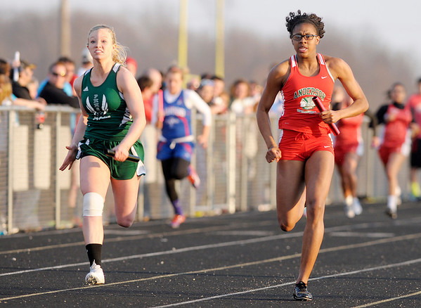 Don Knight | The Herald Bulletin<br /> From left, Pendleton Heights' Tristan VanNatta and Anderson's Shantez Goolsby run the final leg of the girl's 4 by 100 meter relay. Anderson's team of Goolsby, Allison Smitherman, Da'Sha Boyd, and Pearson Newsom finished first.