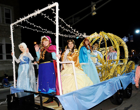 Don Knight    The Herald Bulletin<br /> Disney Princesses wave to the crowd during the Anderson Christmas parade on Saturday.