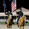 Don Knight | The Herald Bulletin<br /> Hoosier Park outriders carry the American and Indiana flags as the lead the first post parade for the Breeders Crown at Hoosier Park on Saturday.