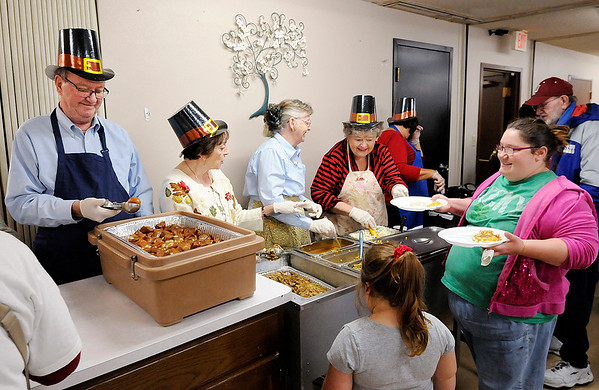 Don Knight |  The Herald Bulletin<br /> Volunteers serve meals during the John Lawson / Fran Wellman Memorial Thanksgiving Dinner at Cross Roads United Methodist Church in Anderson on Tuesday. Wicks donated pies, Family Video donated 40 turkeys, the city provide bus rides and over 100 volunteers cooking, preparing and cleaning made the dinner possible.