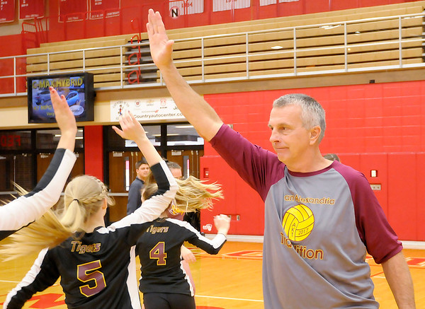 Don Knight | The Herald Bulletin<br /> Alexandria coach Jeff Harmon high fives all of the Tigers before the volleyball semistate at Plymouth High School on Saturday. Harmon is stepping down as coach after 20 years.