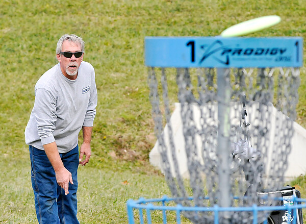 John P. Cleary |  The Herald Bulletin<br /> Players enjoying the warm weather by playing disc golf at the new course in Edgewater Park.