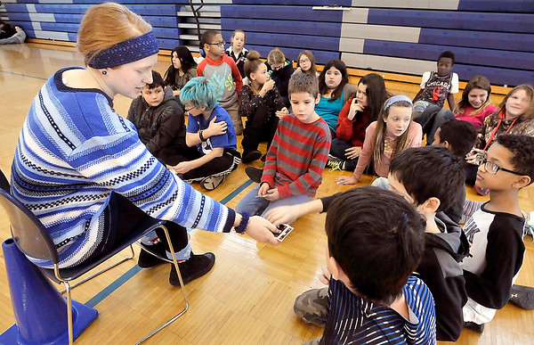 John P. Cleary |  The Herald Bulletin<br /> Megan Moran, an Athlete of Character and Anderson High School volleyball player, hands out her Athlete of Character card to fifth-graders at Erskine Elementary School Friday while talking about the six pillars of character.