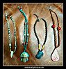 "Lot of four hand made Mexican folk art style necklaces - each is made of woven waxed cording. The one on far left is just over 15"" long and the cords are yellow and black. I do not know what the beads are other than natural materials. The central pendant looks like a tooth but it is not; I think it is carved from white onyx. The second from the left is woven of turquoise blue and brown cords and measures just over 19"" long. The central pendant is about 2"" in length and a little less in width and features an Aztec looking face with headdress and earrings made of clay. It actually looks very old but probably isn't due to its good condition. The second from right is woven of all dark brown cords and measures about 15.5"" long with a central pendant featuring the side view of a Mayan face of clay. It also has two very nice golden colored 1"" long beads woven into the cording on either side of the face. The necklace on the far right is a little over 17"" long and the cords are two shades of brown. The teardrop shaped central pendant is 2.5"" long by about 1.5"" wide and looks like a Mayan hieroglyph in clay. All are quite unique, well made, close securely, in excellent condition and worth much more than the starting price. They can be worn by either male or female."