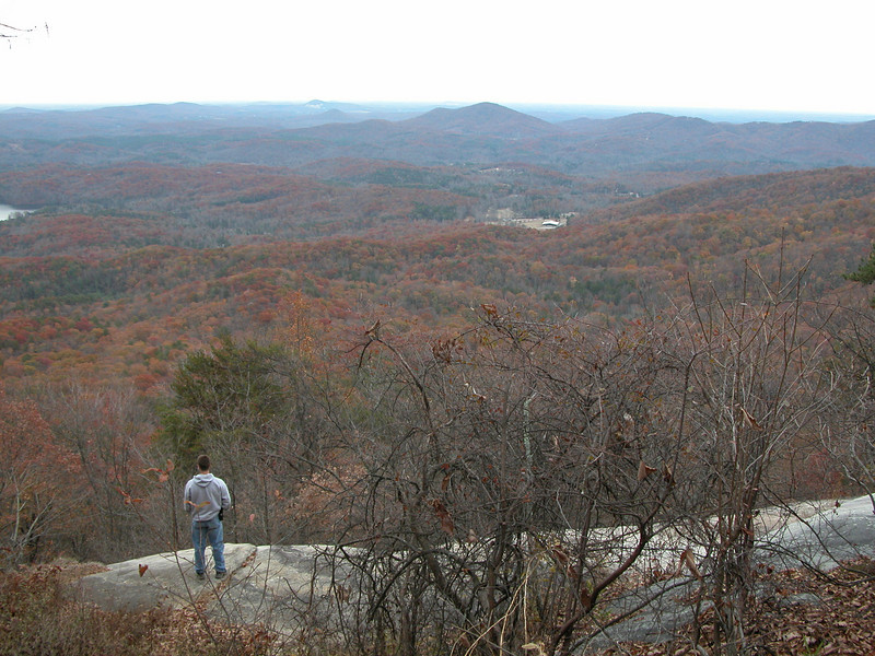 Andrew looking down from (part way up) Table Rock, Pinnacle Mtn. way over the distance barely visable to the left of the more prominent mountains n the center.  Nov. 2008.