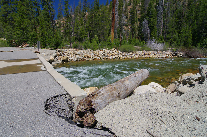 """Damage from Heavy Spring Run-Off to the Bridge over Granite Creek.  I'd say that the water had to come up a good 18""""-2' over the top of the bridge to get this log lodge like it is in this photo."""