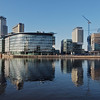 Media City, from the Manchester side of the Manchester Ship Canal, reflected in the canal and basin.