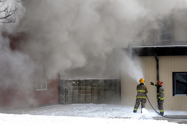 Pat Christman<br /> Firefighters keep the neighboring building, formerly the MnDOT regional headquarters, cool with a hose during Saturday's practice burn of a wooden annex building.