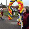 Pat Christman<br /> A runner leaps through a balloon arch as people from the Back Pack Food Program cheer him on Sunday.