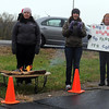Pat Christman<br /> From left, Nina Huntington, Molly Titchenal and Judy Weinzetl cheer on runners from Tichenal's fitness center in Owatonna while staying warm near a fire Sunday near Mount Kato.
