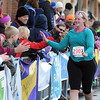 Pat Christman<br /> Krista Petzel of Mankato high fives supporters during the final few feet of her half marathon Sunday.
