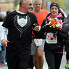 John Cross<br /> Wearing a veil and clutching a bouquet, Rachel Nachreiner of Courtland,  and her father, Mike, cross the finish line of the half-marathon race on Sunday. Nachreiner was joined by her father for the last mile and was married to Steve Page, who also ran in the event, during a ceremony following the race.