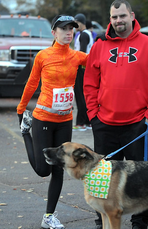 Pat Christman<br /> Parker Greene-Kelly leans against her husband Sean as she stretches before the start of Sunday's Mankato Marathon.