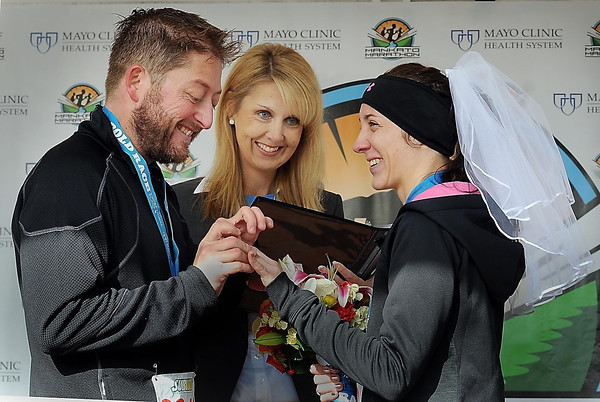 John Cross<br /> Steve Page slips a ring on the finger of Rachel Nachreiner as District Court Judge Krista Jass watches. Jass married the Courtland couple shortly after they both ran in the half-marathon event of the Mankato Marathon on Sunday.