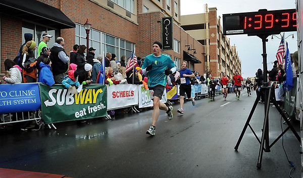 John Cross<br /> Runners in the Mankato Half-Marathon approach the finish line near the Verizon Wireless Center on Sunday.