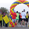 Pat Christman<br /> Marathon runners pass beneath a balloon archway made by a cheer team from the Back Pack Food Program Sunday.