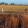 Marathon runners pass by a farm during Sunday's race.
