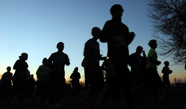 The early morning Sun barely casts an orange glow in the sky as runners depart during the 10K race Sunday.