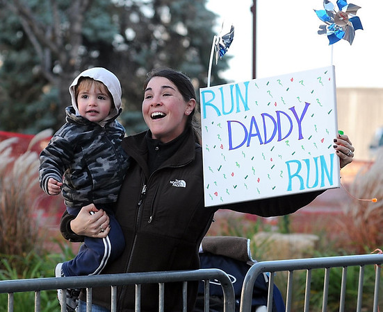 Jen Menzner and her son Parsons cheer on her husband Jon as he nears the finish line of Sunday's Mankato Marathon.
