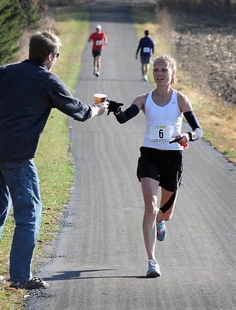 Leslie Anderson takes a cup of water from her husband Karl during Sunday's Mankato Marathon. Anderson was the top women's finisher.