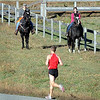 A pair of horseback riders watch marathon winner Paul Donnelly run during Sunday's Mankato Marathon.