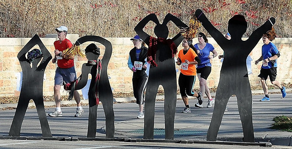 Mankato Half Marathoners run past wooden silhouette race fans in Sibley Park.