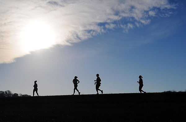 Runners are silhouetted as they run near Mount Kato Sunday.