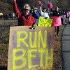 From left, Melissa and Joel Schaefer and Jenn and Kathy Traxler cheer on their friend Beth Schmoll as she runs Sunday's half marathon.