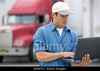 P5.1 / A truck driver sitting in the cabin of the truck holding a paper clip, cellphone or computer.<br /> Choice 5 of 9<br /> <br /> B4AP23 Truck Driver Using Laptop