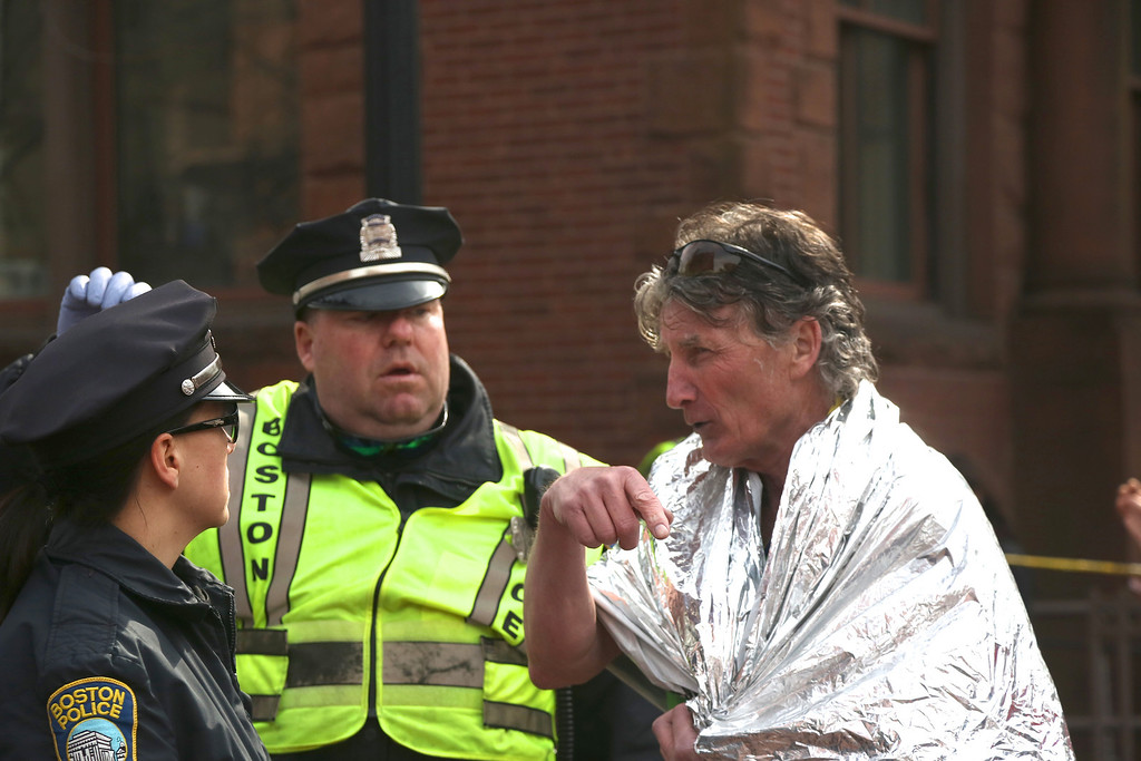 April 15, 2013 - Boston Police officers assist a marathon runner after the explosions at the finish line of the Boston Marathon.  The area, located at Copley Square, was evacuated following two explosions. Photo by Hannah Klarner / BU News Service