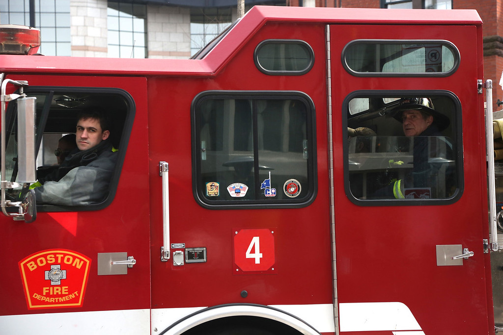 April 15, 2013 - Firefighters sit in their truck on their way to the scene of the Boston Marathon finish line. There were two exploisions at the scene that caused the race to be called off early.  Photo by Hannah Klarner / BU News Service