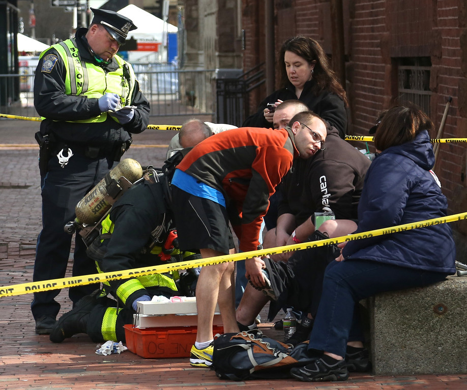 Boston, Mass. April 15- First responders and Boston Police officers care for a victim affected by the three explosions at the finish line of the Boston Marathon.  Photo by Hannah Klarner/ Boston University News Service