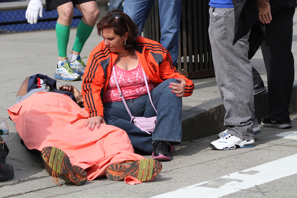 Boston, MA, April 15, 2013: <br /> A woman cares for a Boston Marathon runner outside Hynes Convention Center after two explosions were detonated at the finish line of the 2013 Boston Marathon. <br /> (Photo by Billie Weiss)