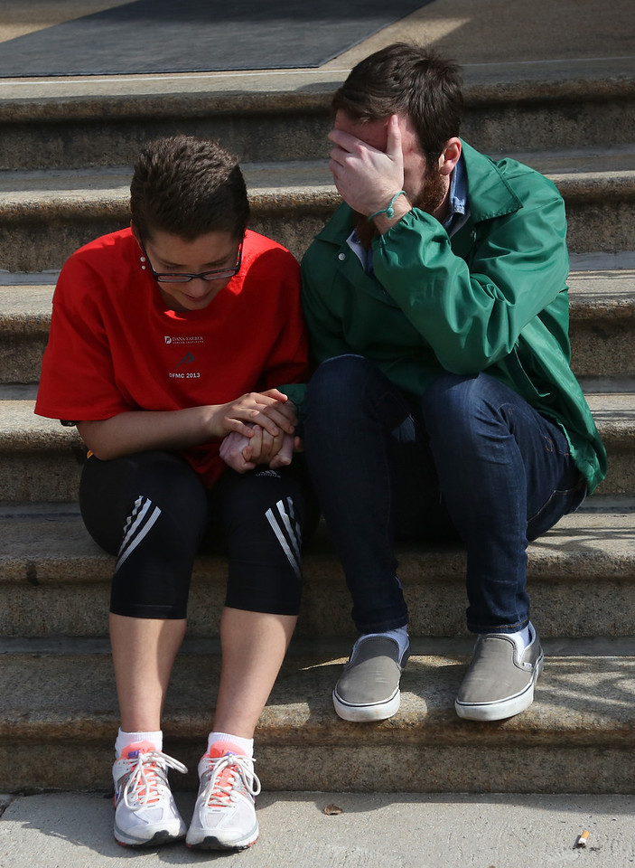 April 15, 2013 - Following the two explosions at the finish line of the Boston Marathon, witnesses sat in prayer on the steps of a house in Boston. There were two explosions that caused the 117th Boston Marathon to be shut down early.  Photo by Hannah Klarner / BU News Service