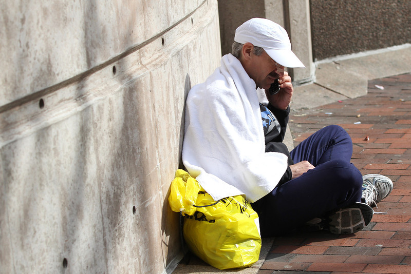Boston, MA, April 15, 2013: <br /> A Boston Marathon runner makes a phone call near Copley Square after two bombs were detonated at the finish line of the 2013 Boston Marathon. <br /> (Photo by Billie Weiss)