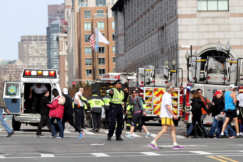 April 15, 2013 - Boston, Massachusetts, United States: A member of the Boston Police Department directs pedestrians outside Hynes Convention Center in Copley Square after two bombs were detonated at the finish line of the 2013 Boston Marathon. (Billie Weiss/Polaris)