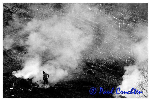 Forestry worker stoking fire, nr Bilsdorf, Luxembourg