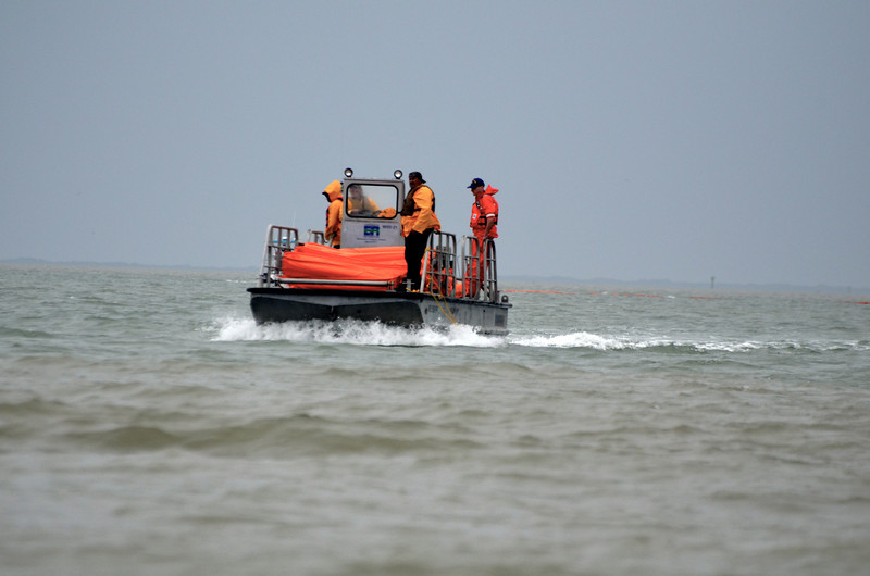 Coast Guard brings out rolls of boom material. <em> Photo credit: Peggy Wilkinson</em>