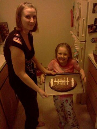 My niece, Amanda, and her daughter Emma, 5, holding Emma's daddy's birthday cake that Emma made for him.<br /> <br /> Photographer's Name: Steve Wallace<br /> Photographer's City and State: Anderson, IN