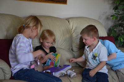 Devyn opening presents, with the help Of McKenna, Carson, and Parker