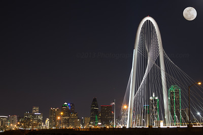 Composite photo of full moon rising over Dallas skyline and Margaret Hunt Hill Bridge.