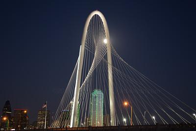 Moon behind Margaret Hunt Hill Bridge, Dallas, Texas skyline.