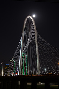 Night show of full moon rising over Margaret Hunt Hill Bridge, with Dallas skyline.