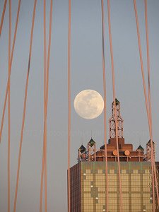 Moon rising over downtown Dallas, Texas with Margaret Hunt Hill Bridge supports in foreground.