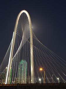 Full moon behind Margaret Hunt Hill Bridge, Dallas, Texas.