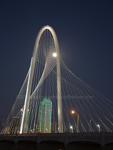 Full moon rising through Margaret Hunt Hill Bridge with Dallas skyline in background.