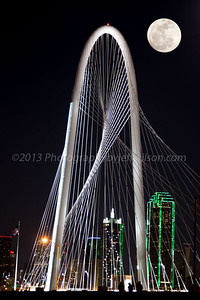 Moon over Dallas skyline with Margaret Hunt Hill Bridge in foreground. Composite photo of bridge and moon.  Bridge shot taken with Canon 6D with 24-105 f4 L IS,  and moon taken with Canon SX50HS at 1200mm.  Moon added with Photoshop Elements 11.
