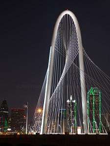 Dallas skyline behind night shot of Margaret Hunt Hill Bridge.