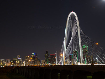 Dallas skyline shot with Margaret Hunt Hill Bridge in foreground with moon peaking out.